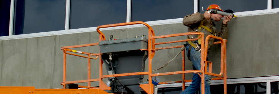 Man Caulking Building